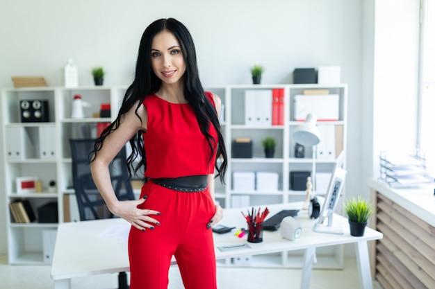 Piękna młoda dziewczyna w czerwonym garniturze stoi w biurze.
