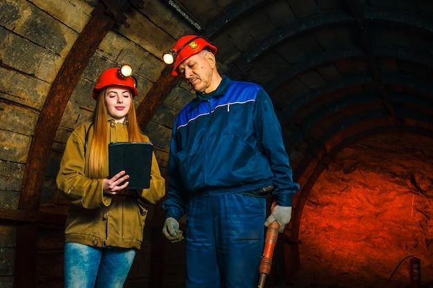 Piękna młoda dziewczyna w czerwonym hełmie iz elektronicznym tabletem w rękach stoi z górnikiem w kopalni węgla. dyskusja na temat biznesplanu.