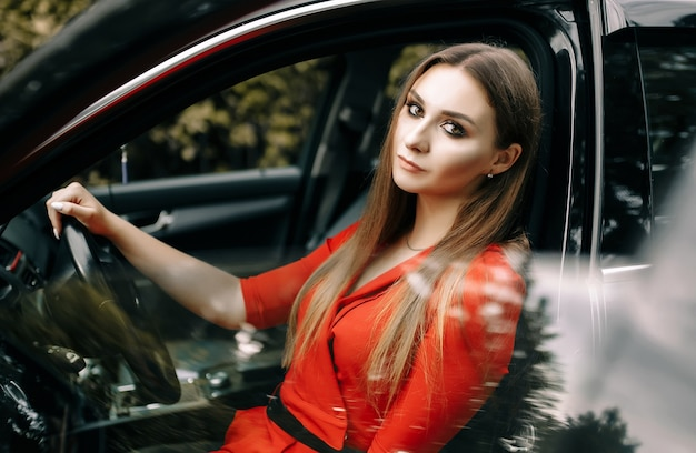 Piękna młoda dziewczyna w czerwonym kombinezonie siedzi za kierownicą czarnego samochodu na pustej drodze w lesie