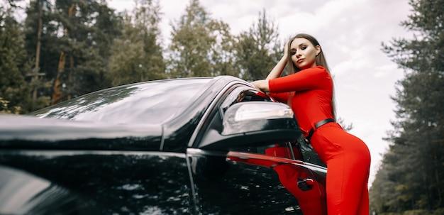 Piękna młoda dziewczyna w czerwonym kombinezonie stoi przy czarnym samochodzie na pustej drodze w lesie