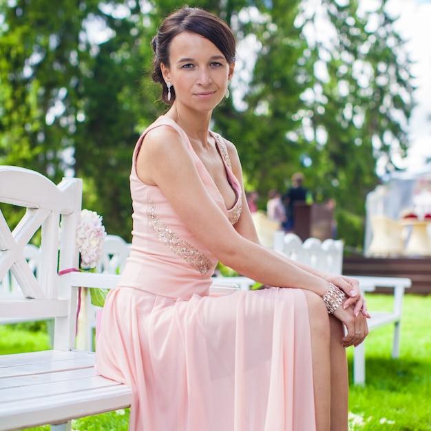 Piękna młoda dziewczyna w długiej sukni przy ceremonią outdoors