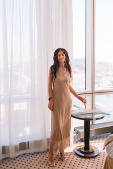 Piękna młoda dziewczyna w długiej sukni w hotelu na imprezie