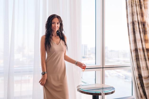 Piękna młoda dziewczyna w długiej sukni w pokoju hotelowym