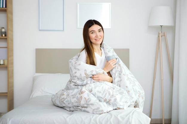 Piękna młoda dziewczyna w dobrym nastroju w piżamie w sypialni