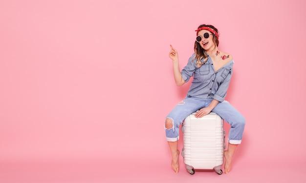 Piękna młoda dziewczyna w dżinsowej koszuli z naklejką wodną tatuaż kwiaty naklejka uśmiecha się i siedzi na walizce