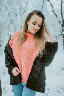 Piękna, młoda dziewczyna w futrze różowy obszerny sweter i dżinsy w lesie mroźna śnieżna zima