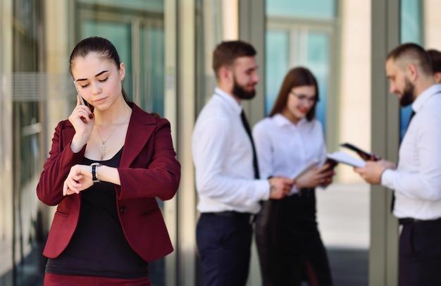 Piękna młoda dziewczyna w garniturze rozmawia przez telefon i patrząc na zegar na powierzchni biurowca i grupy kolegów
