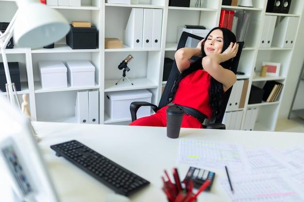 Piękna młoda dziewczyna w hełmofonach siedzi w biurze przy stołem.