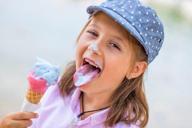 Piękna młoda dziewczyna w kapeluszu jeść lody na zewnątrz