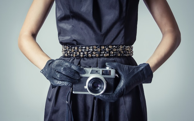 Piękna młoda dziewczyna w klasycznym stylu vintage z analogowym aparatem fotograficznym w dłoniach