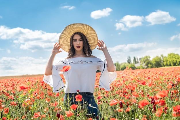Piękna młoda dziewczyna w makowym polu. wolny czas i dobrą pogodę spędza na przyjemności