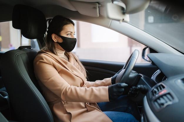 Piękna młoda dziewczyna w masce siedzi w samochodzie i założyła rękawice ochronne.