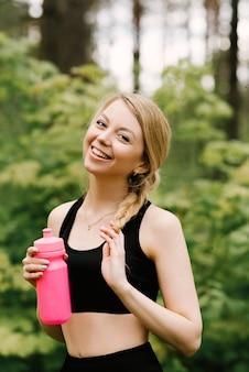 Piękna, młoda dziewczyna w mundurze sportowym z butelką wody, joga i sporty w lesie na świeżym powietrzu