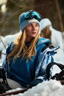Piękna młoda dziewczyna w niebieskim kombinezonie narciarskim i kasku. na głowie znajdują się okulary do jazdy na snowboardzie. pokryty śniegiem krajobraz górski. portret jeźdźca. tak wygląda szczęście.