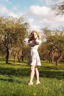 Piękna młoda dziewczyna w parku na wiosnę. portret w pełnej wysokości. zdjęcie pionowe