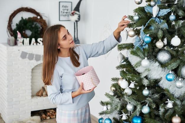 Piękna młoda dziewczyna w piżamie dekorowanie choinki