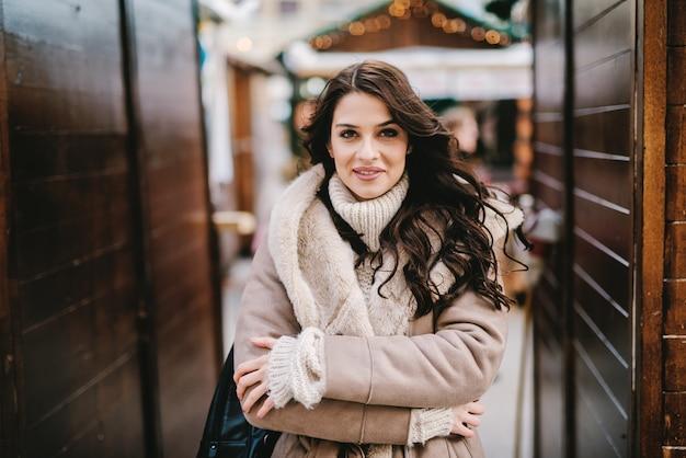 Piękna, młoda dziewczyna w płaszcz zimowy stojąc na ulicy i ciesząc się w miły zimowy dzień. patrząc na aparat i uśmiechając się.