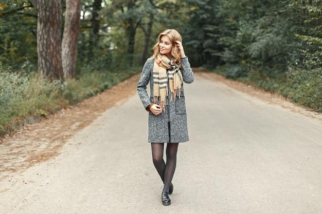 Piękna, młoda dziewczyna w płaszczu vintage i ciepłym szaliku spaceruje po jesiennym parku