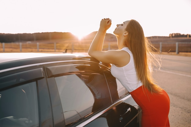 Piękna, młoda dziewczyna w pobliżu samochodu wieczorem w zachodzie słońca