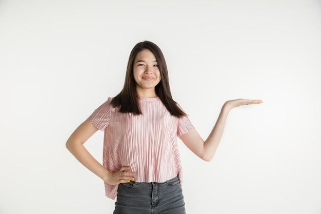 Piękna, młoda dziewczyna w połowie długości portret na białym tle na ścianie białego studia