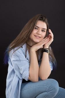 Piękna młoda dziewczyna w przypadkowych ubraniach patrzeje kamerę i ono uśmiecha się