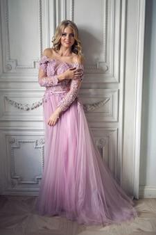Piękna, młoda dziewczyna w różowej koronkowej sukni stojącej przy ścianie w białym pokoju