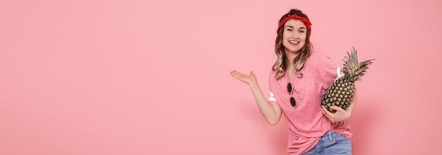 Piękna młoda dziewczyna w różowej koszulce, uśmiechając się z ananasem