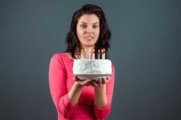 Piękna młoda dziewczyna w różowej sukni trzyma tort w jej rękach z płonącymi świeczkami, zakończenie. gratulacje z okazji urodzin. skopiuj miejsce
