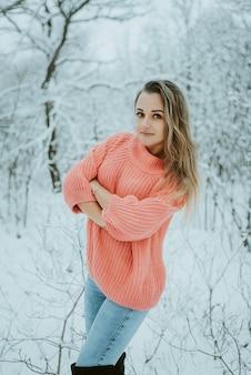 Piękna młoda dziewczyna w różowy obszerny sweter i dżinsy w lesie mroźnej śnieżnej zimy