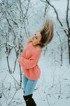 Piękna młoda dziewczyna w różowy obszerny sweter i dżinsy w zimnym, śnieżnym lesie z rozwianymi włosami