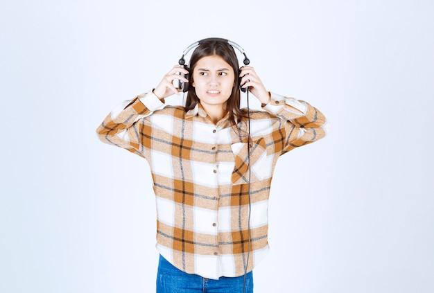 Piękna młoda dziewczyna w słuchawkach męczy się głośną muzyką.