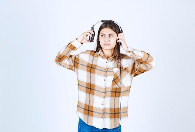 Piękna młoda dziewczyna w słuchawkach, próbując uciec od muzyki.