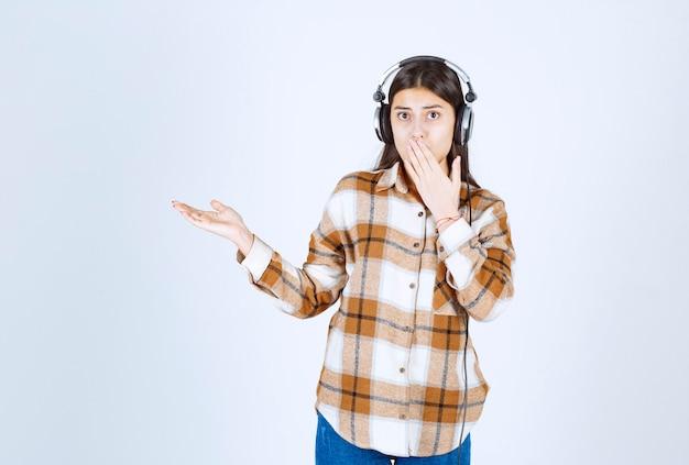Piękna młoda dziewczyna w słuchawkach zakrywając usta na białej ścianie.