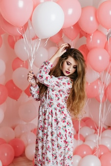 Piękna młoda dziewczyna w sukience wśród wielu różowych kulek.