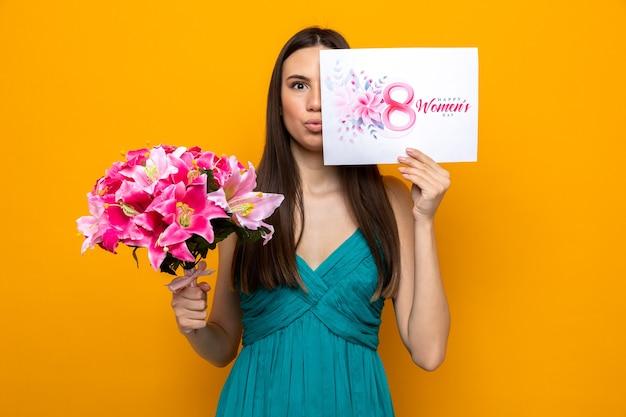 Piękna młoda dziewczyna w szczęśliwy dzień kobiety trzyma bukiet pokrytą twarzą z pocztówką odizolowaną na pomarańczowej ścianie