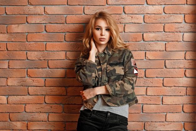 Piękna, młoda dziewczyna w wojskowej kurtce w pobliżu czerwonej cegły