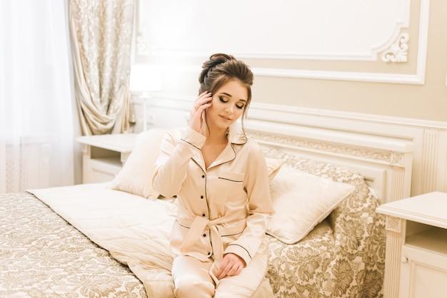 Piękna młoda dziewczyna w złotej piżamie w luksusowym pokoju ze stylowymi włosami i makijażem. poranek panny młodej