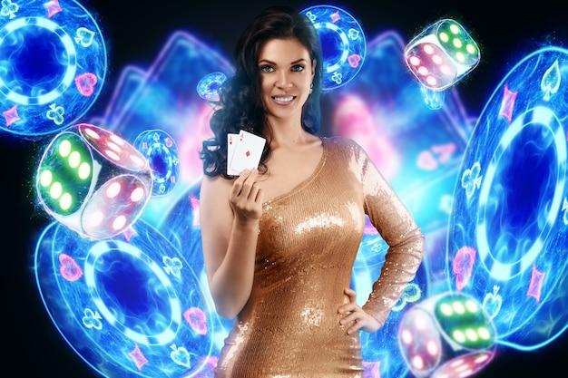 Piękna młoda dziewczyna w złotej sukience trzyma w rękach karty do gry, neonowy napis kasyna, karty i kości. koncepcja banera dla kasyna, pokera, ulotki, hazard, krupier, nagłówek witryny.