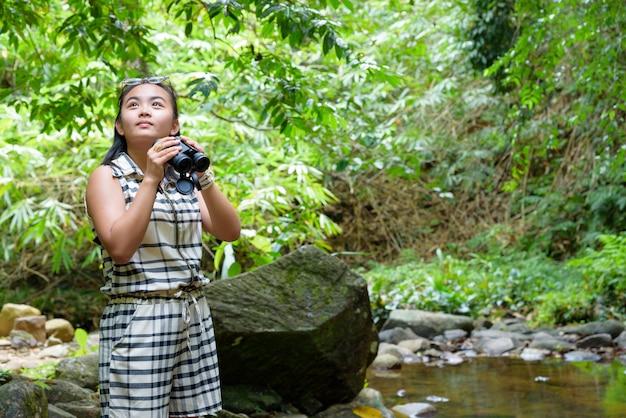 Piękna młoda dziewczyna wędrująca za pomocą lornetki szuka ptaków w tropikalnym lesie w pobliżu wodospadów w tajlandii