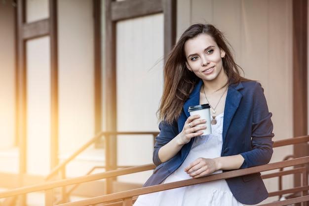 Piękna młoda dziewczyna wychodzi z kawiarni z kawą na wynos w ręku