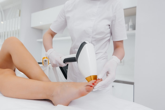Piękna młoda dziewczyna wykona zabieg depilacji laserowej przy użyciu nowoczesnego sprzętu w zbliżeniu salonu spa. salon piękności. pielęgnacja ciała.