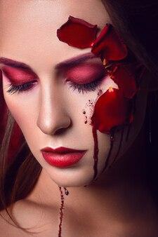 Piękna młoda dziewczyna z aplikacją czerwonych róż kwitnie na twarzy i płynącą krwią