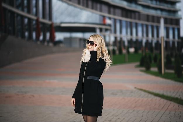 Piękna młoda dziewczyna z blond falistymi włosami w czarnym płaszczu na nowoczesne budynki