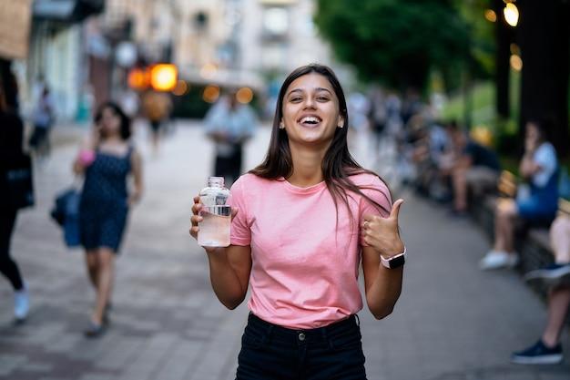 Piękna młoda dziewczyna z butelką wody