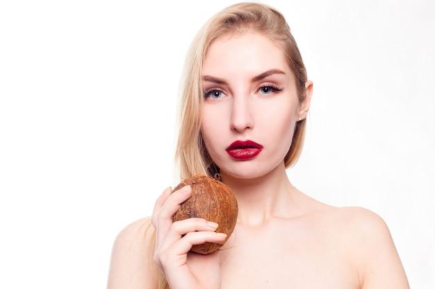 Piękna młoda dziewczyna z czystą skórą z kokosem w dłoni