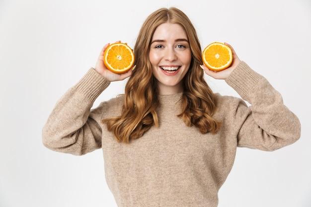 Piękna młoda dziewczyna z długimi blond kręconymi włosami, ubrana w sweter stojący na białym tle nad białą ścianą, pokazująca plasterki pomarańczy