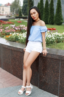 Piękna, młoda dziewczyna z długimi czarnymi włosami w letniej bluzce i białych spodenkach w pobliżu kwiatów