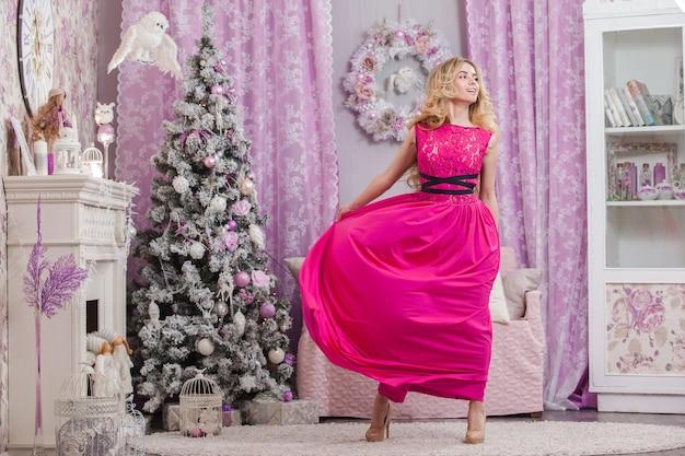 Piękna, młoda dziewczyna z długimi falowanymi włosami w różowej sukience