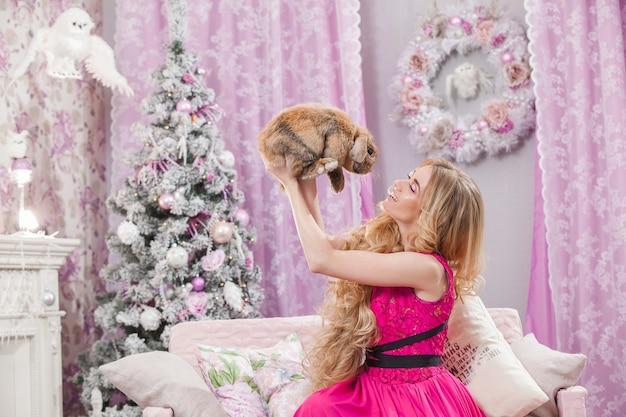 Piękna, młoda dziewczyna z długimi falującymi włosami w różowej sukience na tle choinki z królikiem