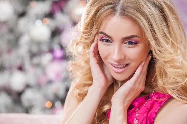 Piękna, młoda dziewczyna z długimi falującymi włosami w różowej sukience na tle choinki